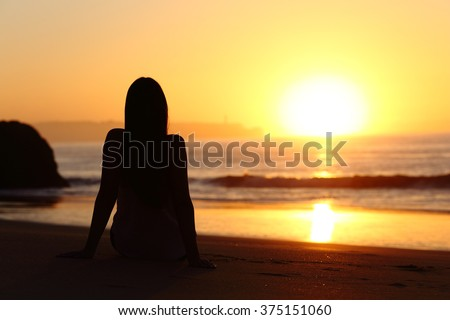 Back view of a woman silhouette sitting on the sand of a beach watching sun at sunrise with the horizon and ocean in the background - stock photo