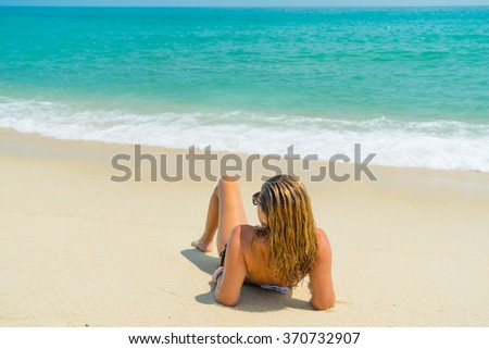 Back view of a Woman sitting on the beach