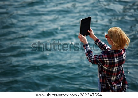Back view of a woman taking picture with a digital tablet camera standing against sea background on the beach, female tourist standing on coastline photographing nature view, wing in sunny day - stock photo