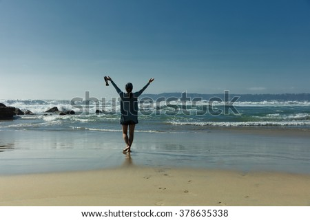 Back view of a woman walking barefoot into ocean with arm raised towards bright sky.