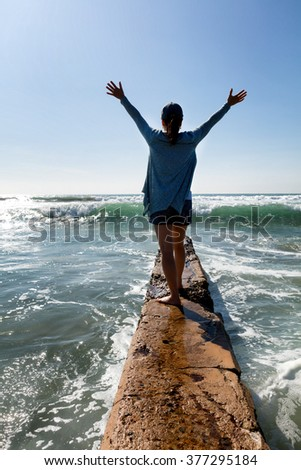 Back view of a woman walking break wall into ocean with arm raised towards bright sky.  - stock photo