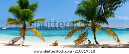 Back view of a young beautiful woman relaxing at white sand tropical beach while kids playing on background