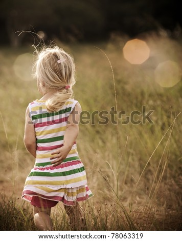 Back view of a young blond girl running happily in an open field, graded with a nostalgic tone
