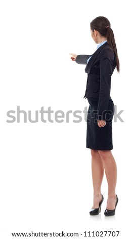 Back view of a young business woman pointing with her right hand, on white background