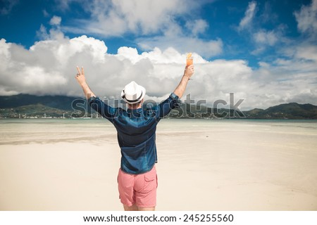 Back view of a young casual man at the seaside holding both hands in the air celebrating life and freedom. He is  holding a cocktail in his right hand. - stock photo