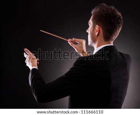 Back view of a young composer directing with his baton, on black background - stock photo