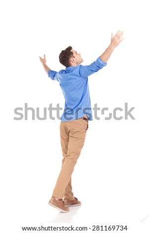 Back view of a young fashion man holding his hands up, celebrating. - stock photo