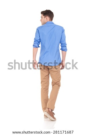 Back view of a young fashion man walking on isolated background looking to his side.