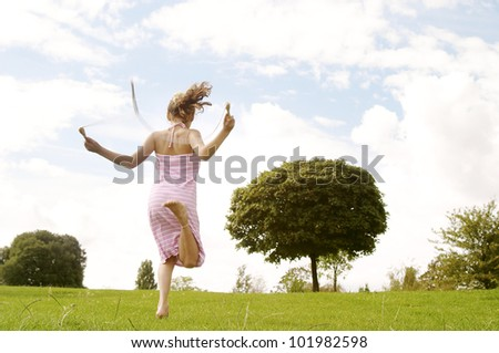 Back view of a young girl skipping in the park with a rope. - stock photo