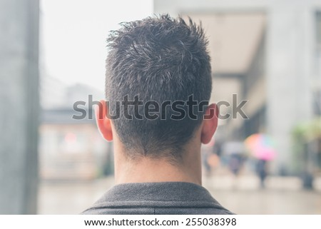Back view of a young handsome man with short hair posing in the city streets - stock photo