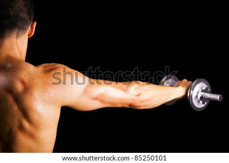 Back view of a young male bodybuilder doing heavy weight exercise with dumbbells against dark background - stock photo