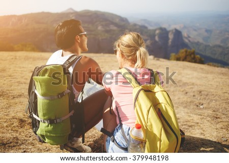 Back view of a young man and woman enjoying amazing nature landscape during their summer trip overseas, two wanderers sitting on a high mountain while resting after hiking in beautiful sunny day - stock photo
