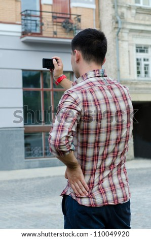 Back view of a young man photographing a building with a small compact digital camera - stock photo