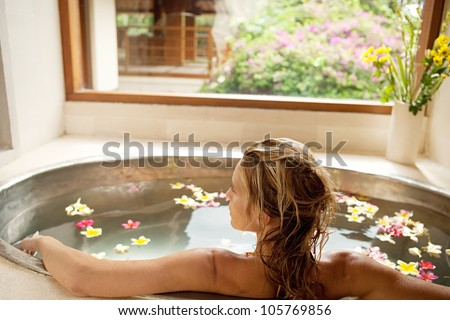 Back view of a young woman bathing in a health spa's flower bath.