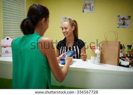 Back view of a young woman buyer calculated for purchase through card reader while standing in modern shop interior, beautiful female seller serves customer in the store with cosmetics product  - stock photo
