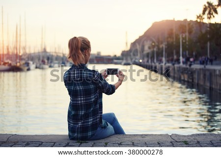 Back view of a young woman making self portrait on smart phone digital camera while sitting near sea port, female photographing herself on cell telephone for social network picture during rest outside - stock photo