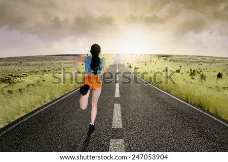 Back view of a young woman running on a rural road during sunset - stock photo