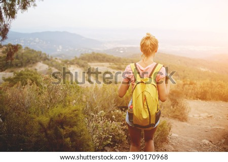 Back view of a young woman traveler with yellow rucksack is enjoying beautiful landscape during her hike, blonde female wanderer is looking away while is standing on a high mountain in warm summer day - stock photo