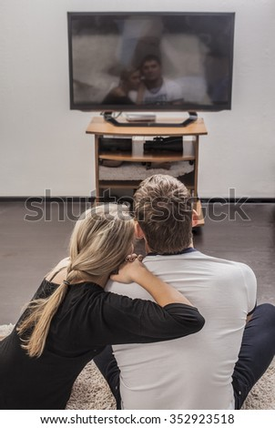 back view of adult caucasian couple sitting on white sofa and floor at their apartment and looking modern tv screen of their new apartment. Copy space for inscription. Embracing man and woman at home - stock photo
