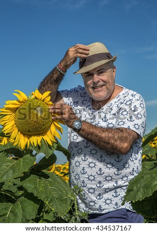 back view of  adult man in sunhat in sunflower field