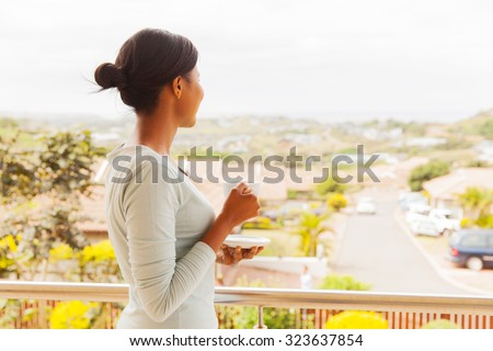 back view of african woman drinking tea on balcony - stock photo