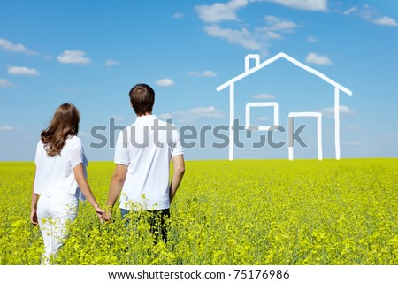 Back view of amorous couple in yellow meadow looking at drawn house