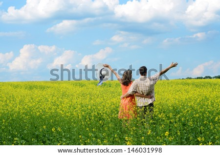Back view of amorous couple walking in yellow meadow at summer