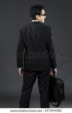 Back view of an Asian business man holding a briefcase. Dark grey background   - stock photo