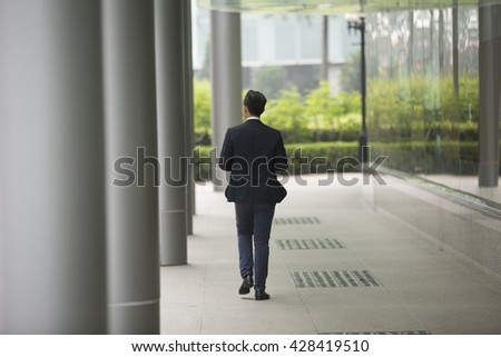 Back view of an Asian businessman walking away from camera in the city.