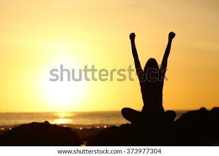 Back view of an excited euphoric woman silhouette raising arms and looking orange sun at sunrise in the beach with the ocean in the background - stock photo