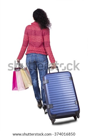 Back view of an Indian woman walking in the studio while carrying shopping bags and suitcase - stock photo