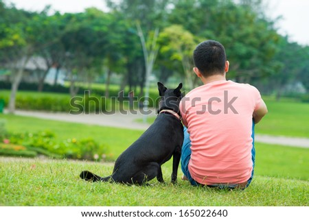 Back view of an owner sitting on the green lawn with his black dog  - stock photo