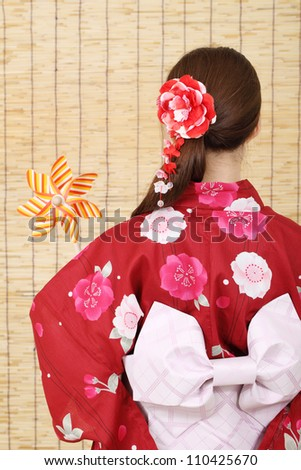 Back view of asian woman in clothes of kimono with toy pinwheel - stock photo