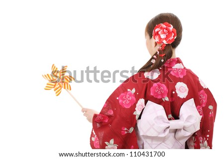 Back view of asian woman in traditional clothes of kimono holding toy pinwheel - stock photo