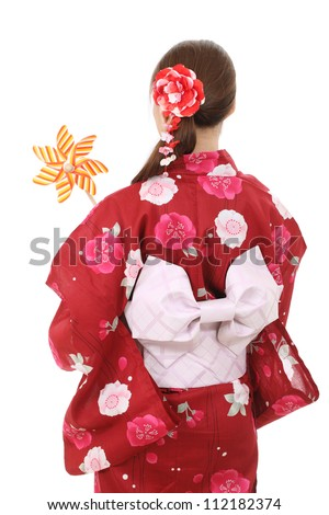 Back view of asian woman in traditional clothes of kimono holding toy pinwheel