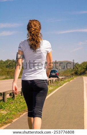 Back view of athletic young woman with sportswear and arm support band for smartphone walking outdoors. Modern healthy lifestyle concept. - stock photo
