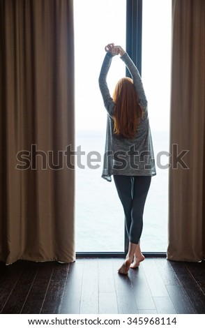 Back view of attractive slim young lady with beautiful long red hair standing barefoot and stretching at the big window - stock photo