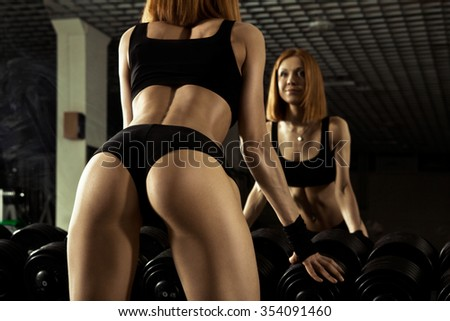 Back view of attractive young topless girl exercising in gym