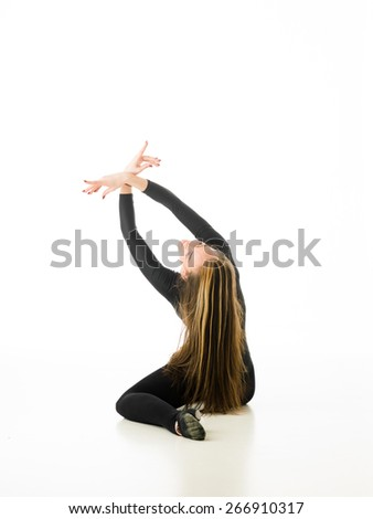 back view of ballerina sitting on floor holding hands up crossed, on white background