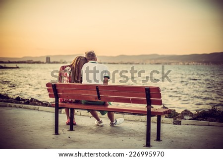 Back view of beautiful love couple sitting outdoors on a bench looking the sea and sky in background