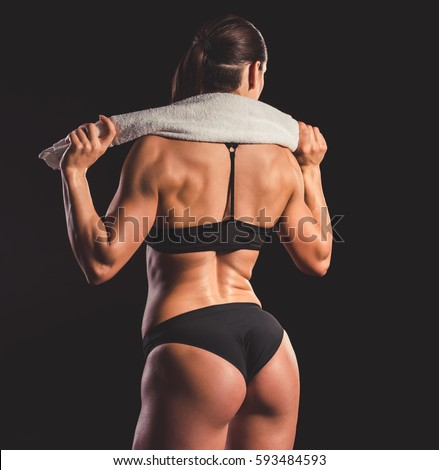Back view of beautiful strong muscular woman in black underwear holding a towel, on dark background