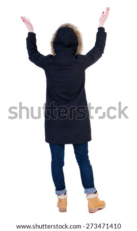Back view of Beautiful woman in parka looking at wall and Holds  hand up.  young blonde girl standing. Rear view people. Isolated over white background. - stock photo