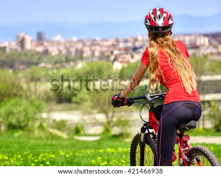 Back view of bikes cycling girl. Girl rides bicycle. Girl wearing red in cycling. Cycling is good for health. Cyclist looking at city.  - stock photo