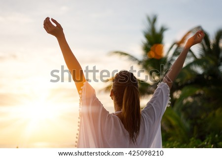 Back view of blissful woman at tropical beach enjoying relax, freedom and vacation.  Female raising arms towards the sun on beautiful sunrise. Summer happiness and leisure. - stock photo