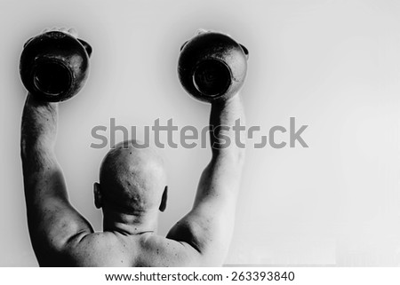 Back view of bold man lifting up two kettlebells.. Black-and-white, strong blur background, horizontal - stock photo