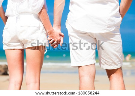 back view of bottom of man and woman romantic couple in white clothes holding hands and walking on tropical beach
