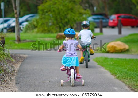 Back view of boy and girl riding bicycles in a park - stock photo