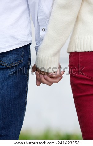 Back view of boyfriend and girlfriend holding hands outdoors