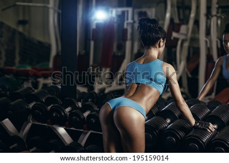 Back view of brunette sexy fitness girl in blue sport wear with perfect body in the gym posing - stock photo