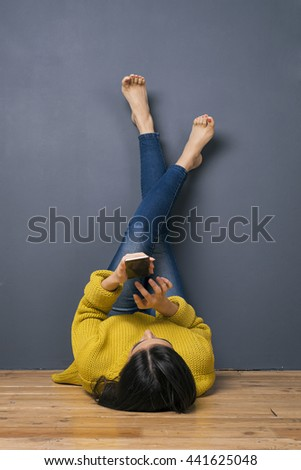 Back view of brunette using cell while lying on back with crossed raised legs on grey wall
